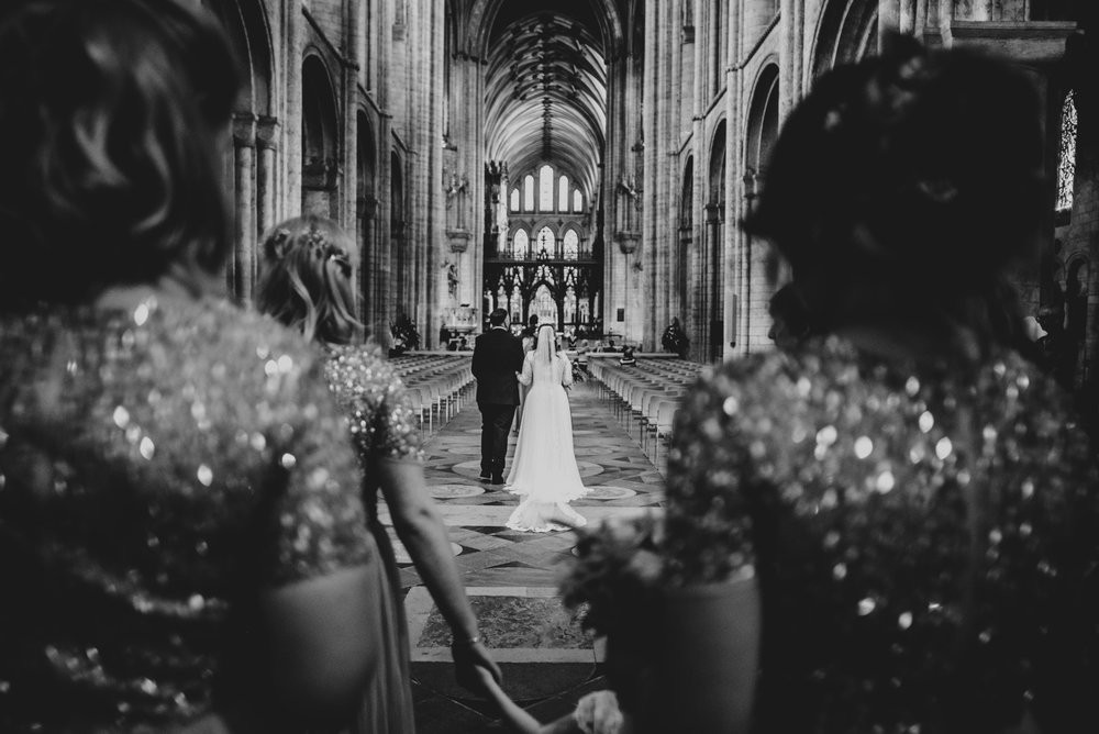 View between Bridesmaids of Bride walking down aisle in Ely Cathedral Cambridge, Essex Documentary Wedding Photographer