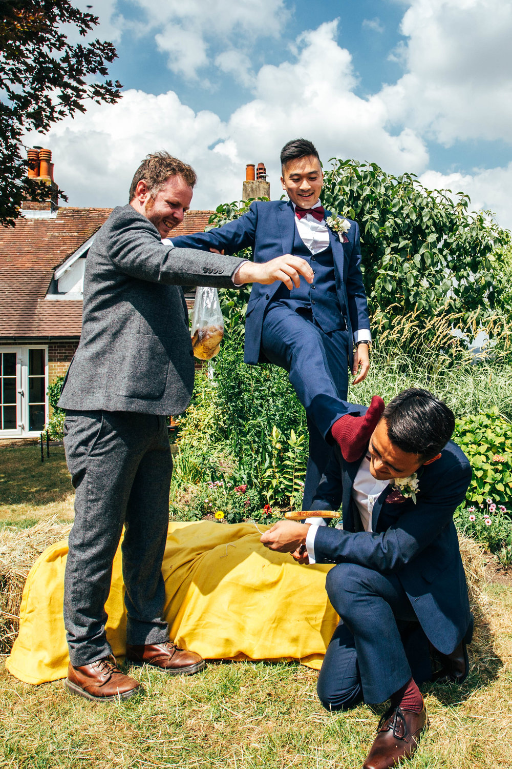 Groom rubs socked foot in Ushers face during pre-wedding game at The Long Barn, Essex Documentary Wedding Photographer