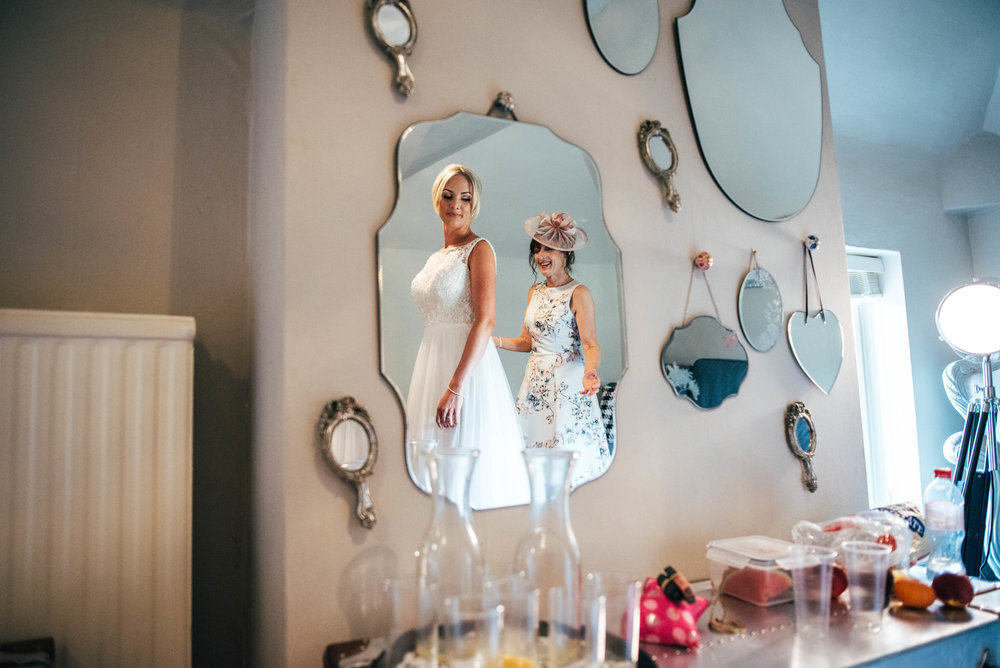 Bride and her mum in mirrors during prep at Parklands Quendon Hall.  Essex documentary wedding photographer