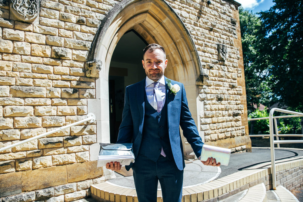Best Man hold two handbags outside church, Essex Documentary Wedding Photographer