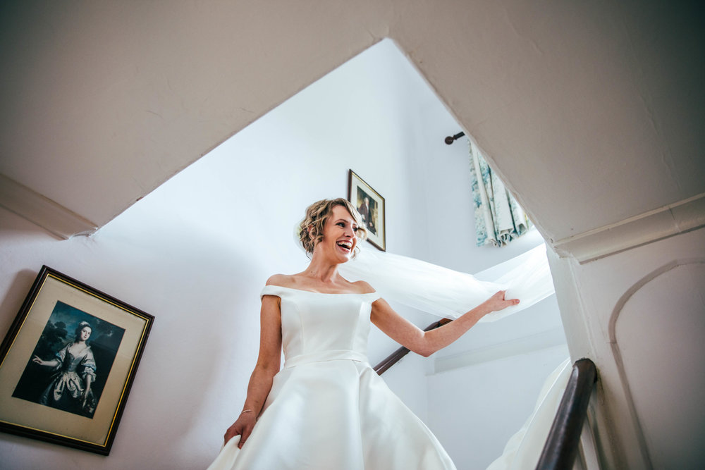 Bride on stairwell on way to ceremony at Hedingham Castle, Essex Documentary Wedding Photographer