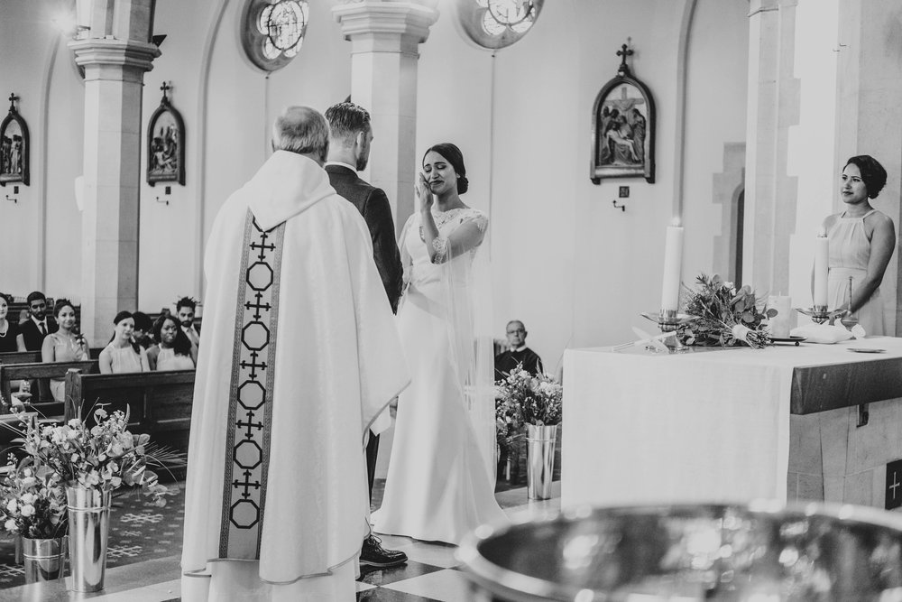 Bride wipes away tear during ceremony in East London Church, Essex Documentary Wedding Photographer