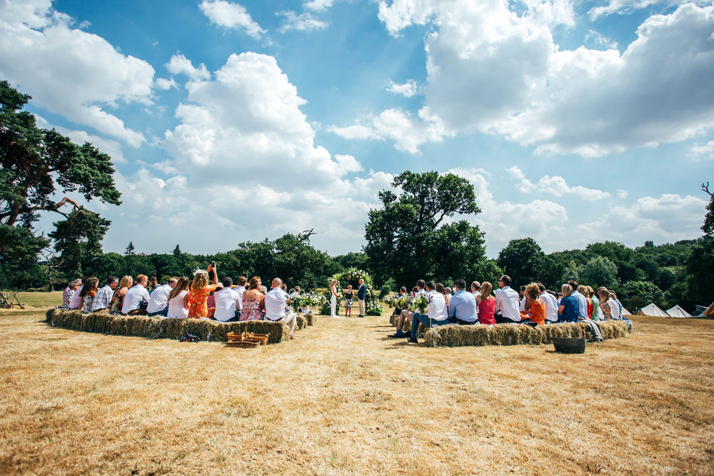 Guests sit on hay bales under fluffy clouds for diy back garden wedding Essex Documentary Wedding Photographer