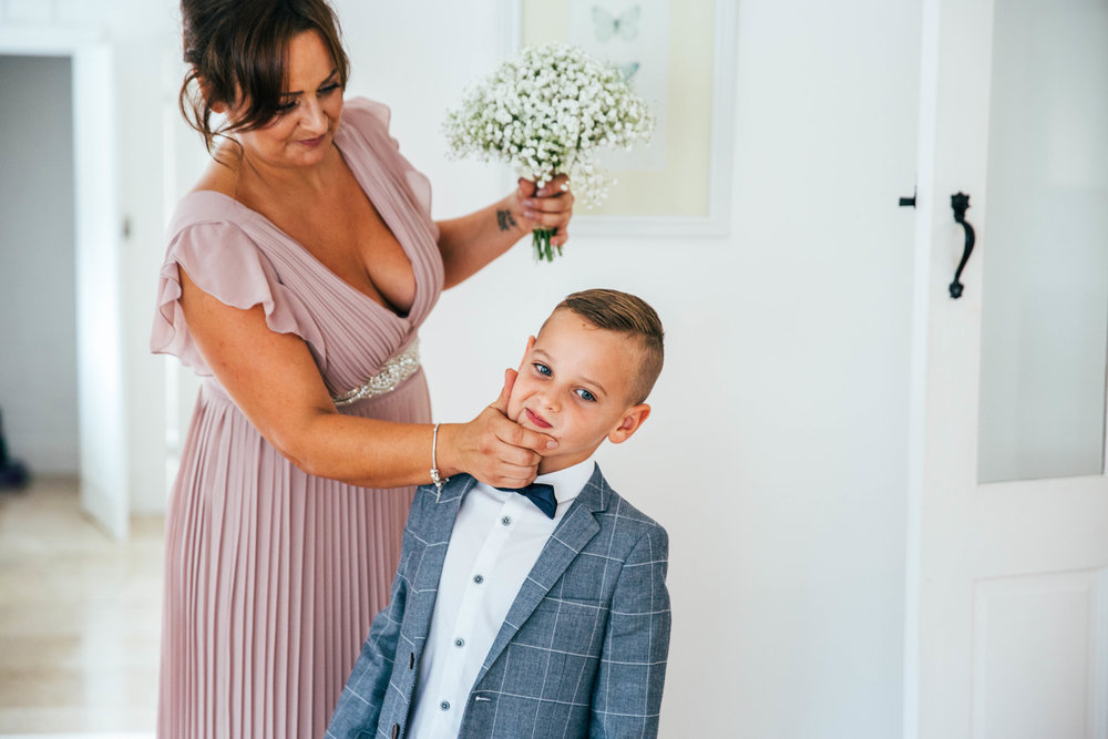 Bridesmaid wipes son's face before ceremony at Blake Hall, Ongar Essex Documentary Wedding Photographer