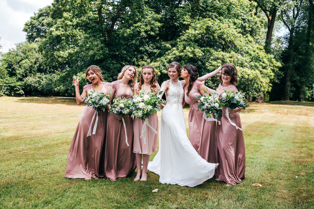 Playful bride and bridesmaids at The Long Barn.  Essex Documentary Wedding Photographer