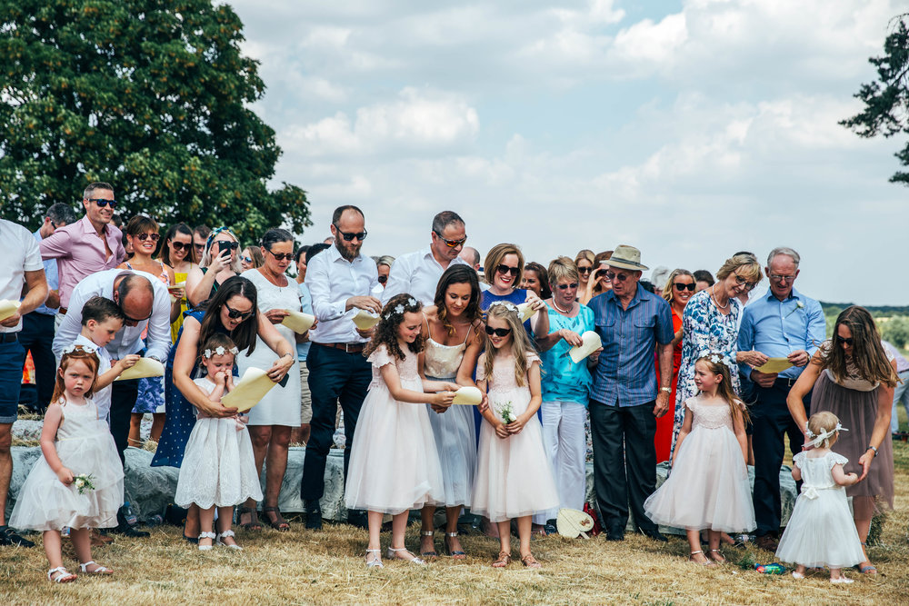Wedding guests read song lyrics during outdoor, diy, farm wedding Essex Documentary Wedding Photographer