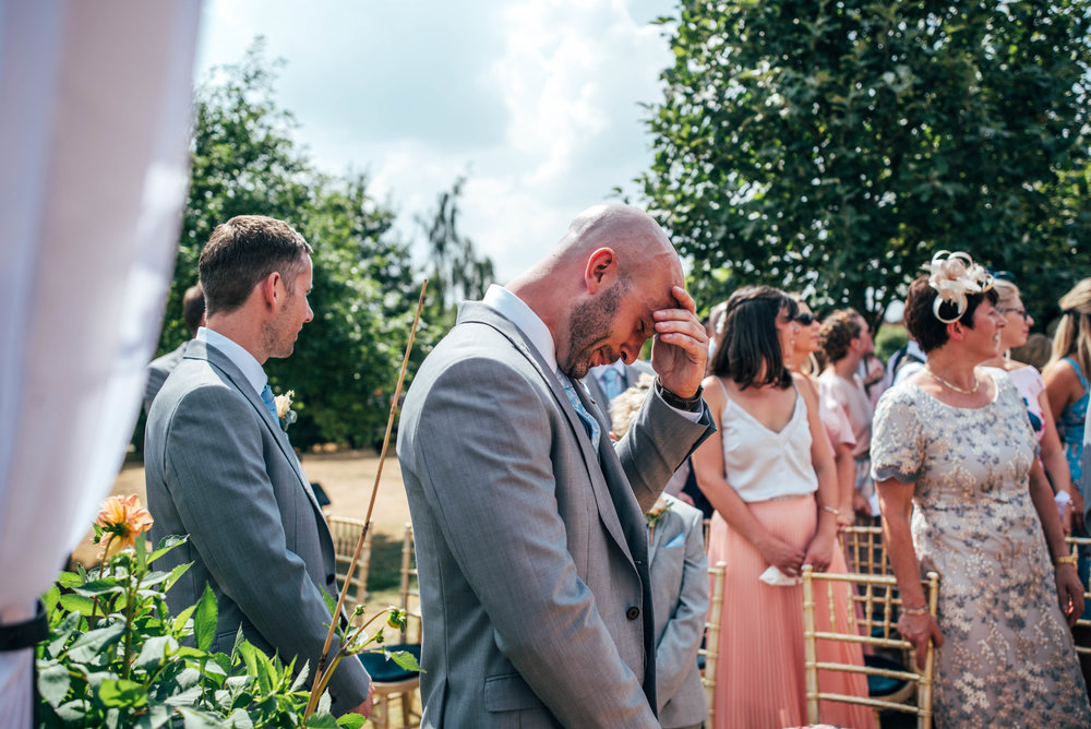 Emotional Groom as Bride walks down aisle in outdoor, diy back garden wedding, Essex Documentary Wedding Photographer