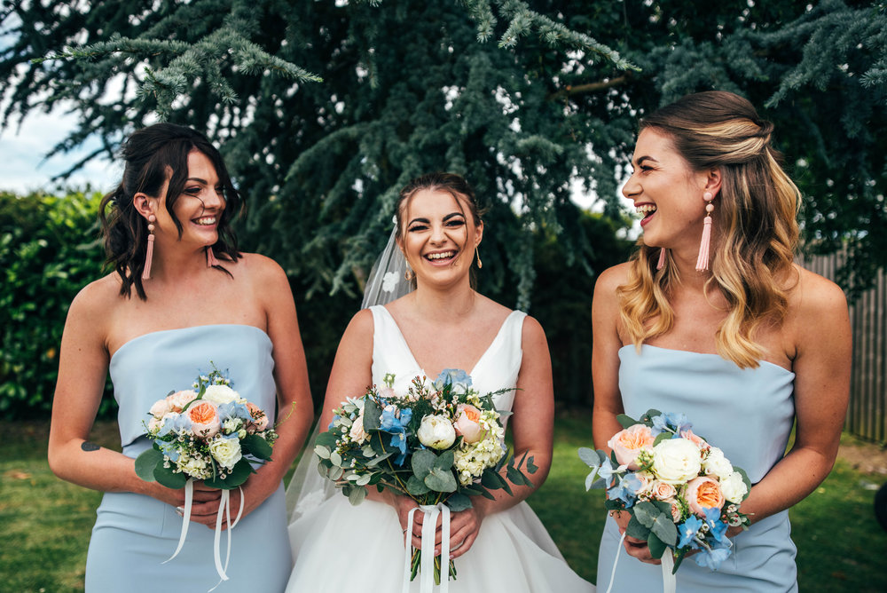 Bride with Bridesmaids in Blue laugh in garden for Ratsbury Barn Wedding, Essex Documentary Wedding Photographer