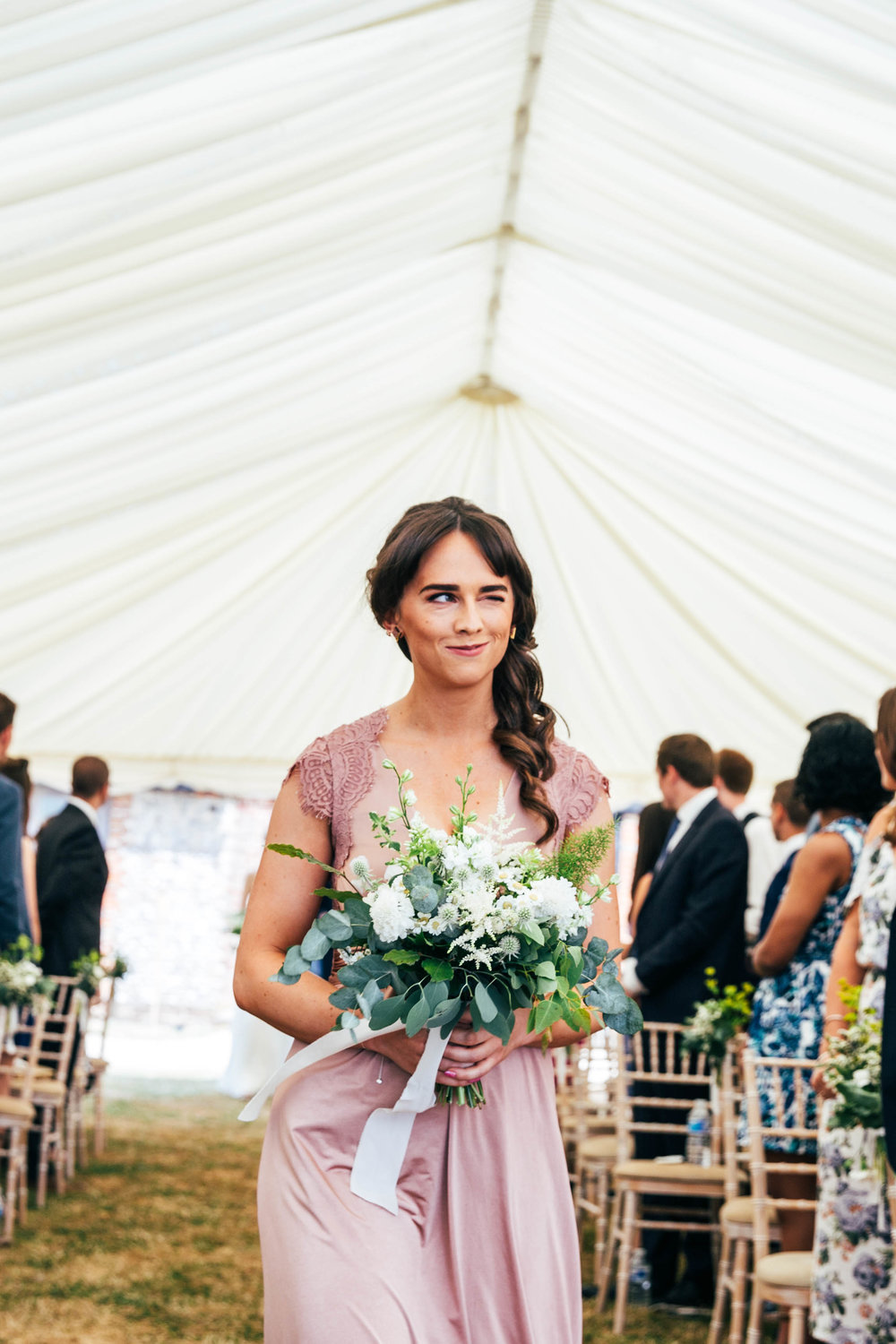 Bridesmaid winks as she walks down the aisle, The Long Barn, Essex Documentary Wedding Photographer