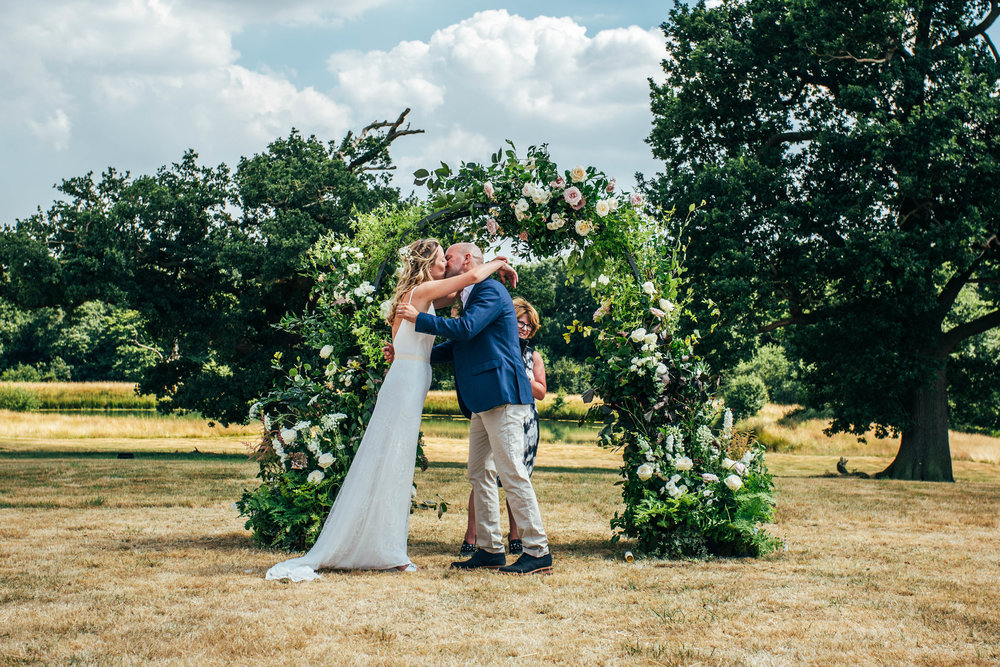 Bride and Groom kiss under Flower Arch for back garden, diy wedding Essex Documentary Wedding Photographer