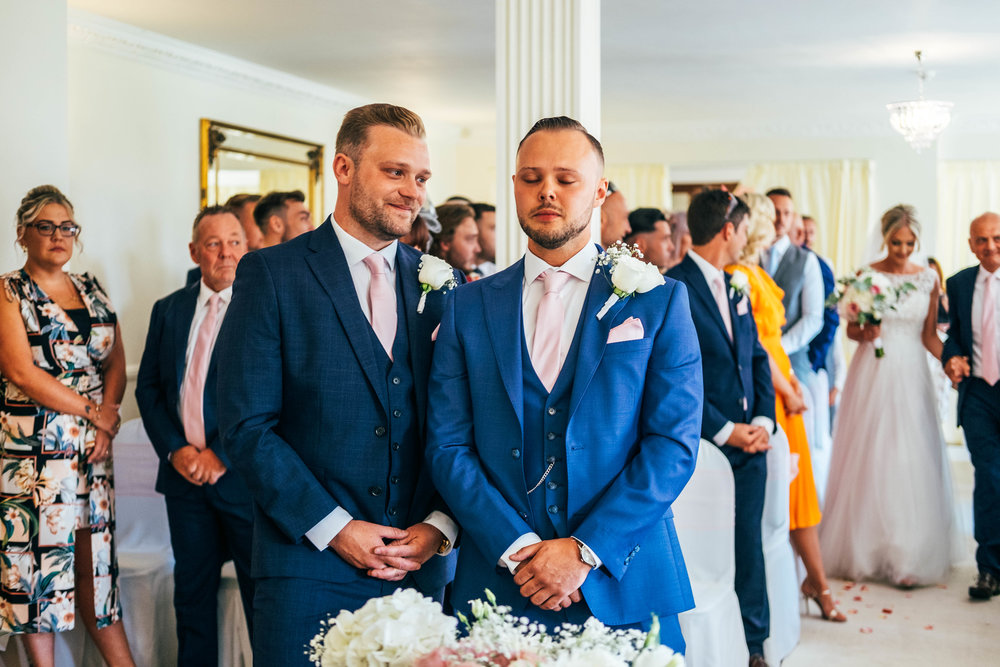 Emotional Groom stands with Best Man for entrance of the Bride at Parklands, Quendon Hall, Essex Documentary Wedding Photographer