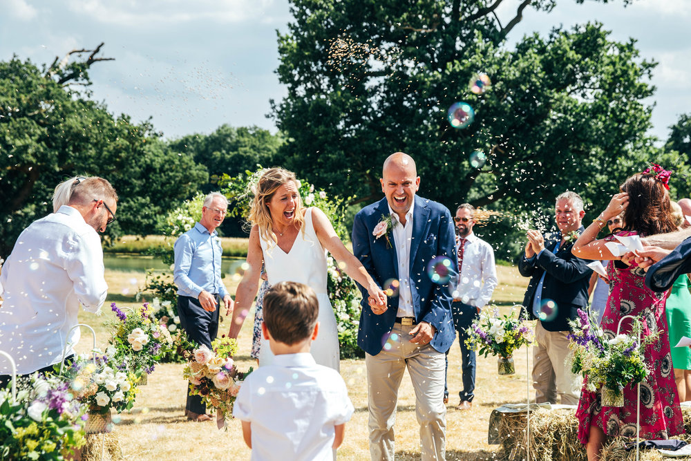 Guests throw confetti and blow bubbles at Bride and Groom in Boho, DIY, Back Garden wedding, Essex Documentary Wedding Photographer