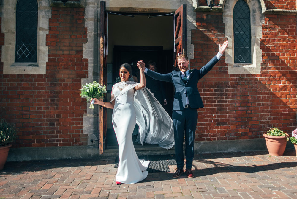 Bride and Groom raise arms in triumph as they exit East London Church, Essex Documentary Wedding Photographer
