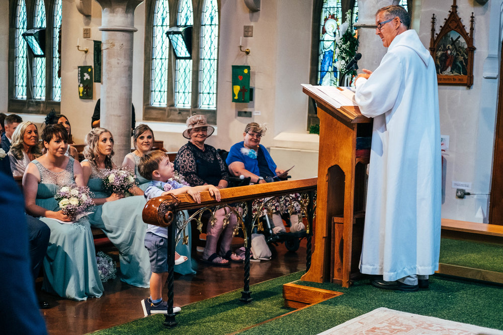 Little boys looks up at vicar during church wedding, Essex Documentary Wedding Photographer
