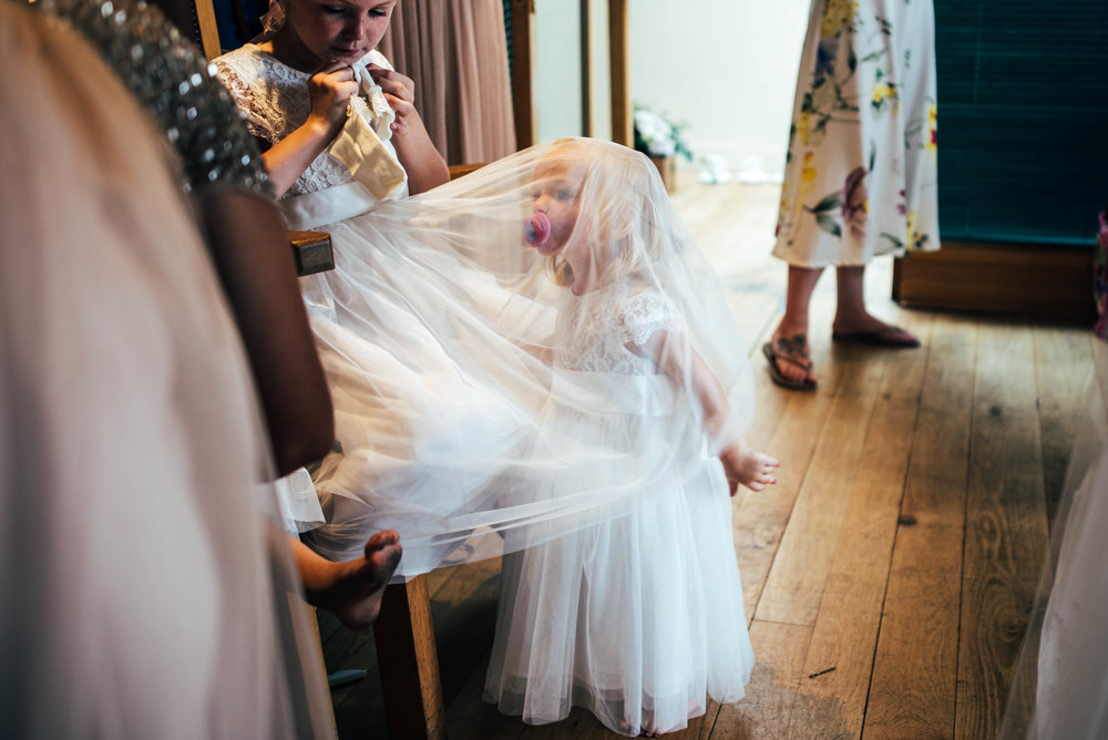 Flower girl hides under veil at Stock Brook Manor, Billericay.  Essex Documentary Wedding Photographer