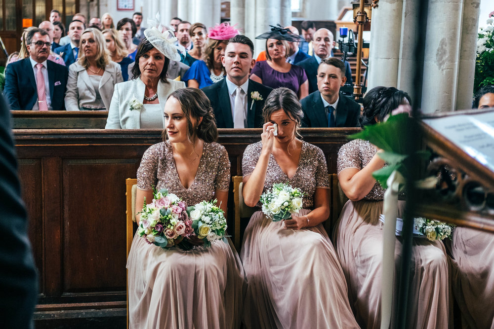 Bridesmaids cry during ceremony at St Mary's Church, Bocking for Fennes, Braintree Wedding. Essex Documentary Wedding Photographer