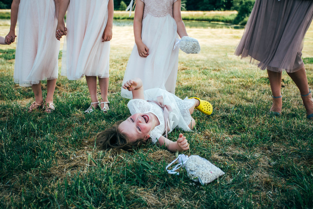 Flower Girl laughs on floor for DIY Back Garden Wedding Essex Documentary Wedding Photographer