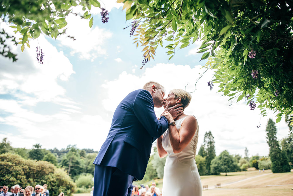 Bride and Groom kiss, lawn ceremony at Ashdown Park Hotel, Essex Documentary Wedding Photographer