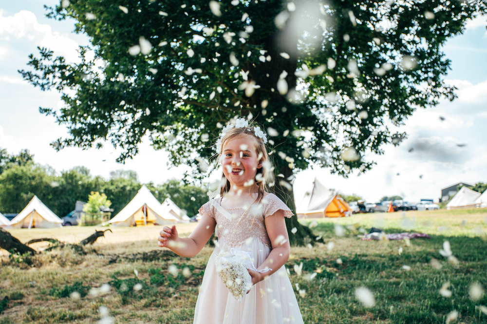 Flower Girl throws confetti at camera, DIY Boho Wedding, Essex Documentary Wedding Photographer