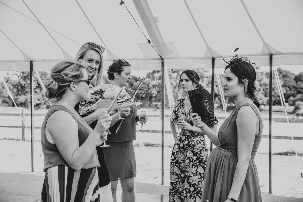 Wedding guests fan themselves Summer Wedding, Essex Documentary Wedding Photographer
