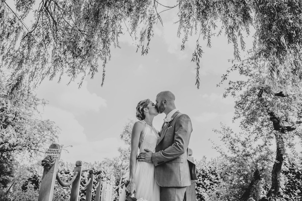 Bride and Groom kiss framed by willow tree DIY Boho Tipi wedding Essex Documentary Wedding Photographer