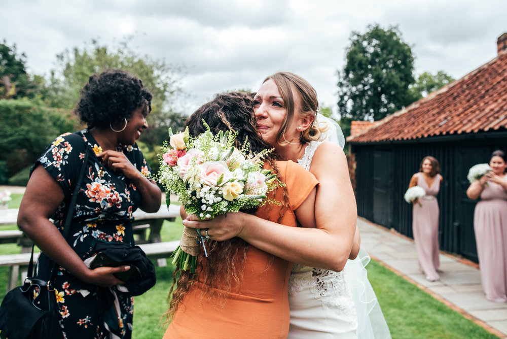 Tearful Bride hugs friend at Blake Hall, Ongar.  Essex Documentary Wedding Photographer