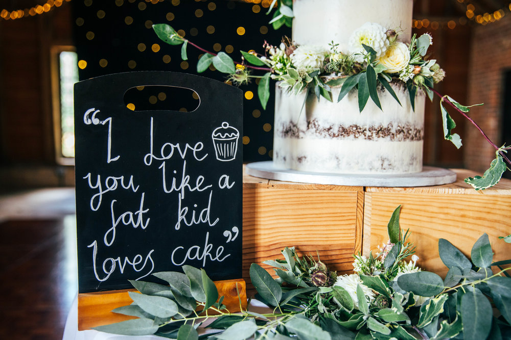 I love you more than a fat kid likes cake. Wedding Cake sign at The Long Barn.  Essex Documentary Wedding Photographer