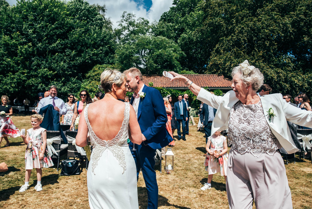 Wedding guest throw confetti over Bride and Groom.  Ashdown Park Hotel.  Essex Documentary Wedding Photographer