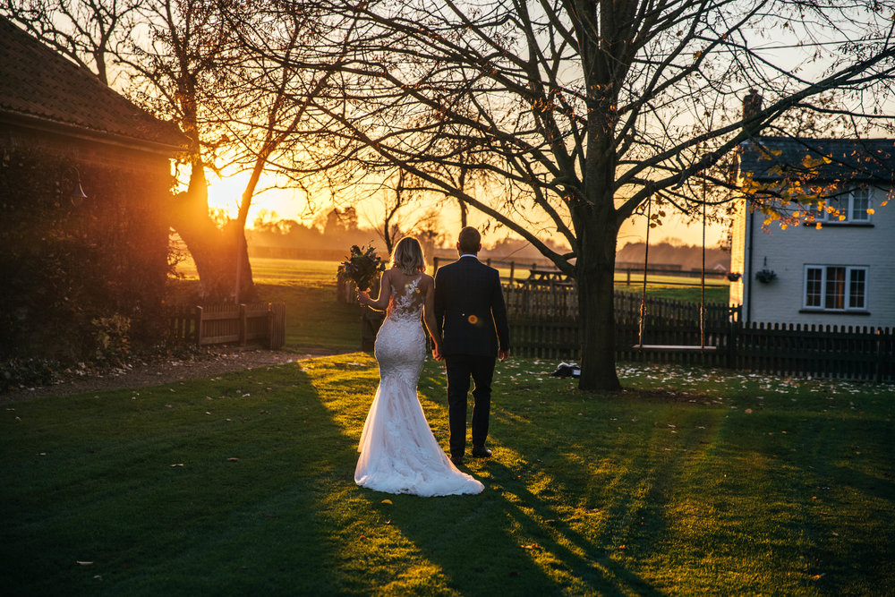 Bride and Groom walk into Autumn Sunset at The Granary Estates, Woodditton.  Essex Documentary Wedding Photographer