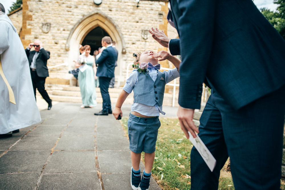 Little boy high fives guest outside church.  Essex Documentary wedding Photographer