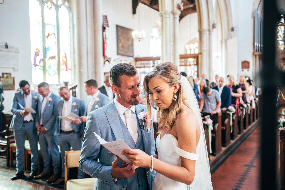 Groom steals a look at his Bride at St Marys Church, Bocking for Fennes, Braintree Wedding.  Essex Documentary Wedding Photographer