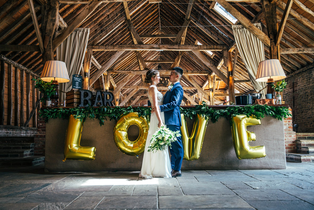 Bride and Groom LOVE Balloons in The Long Barn.  Essex Documentary Wedding Photographer