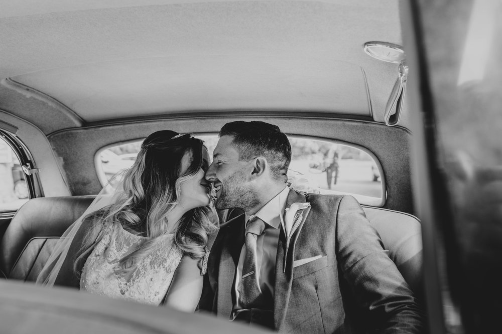 Bride and Groom kiss in back of wedding car at Blake Hall, Ongar.   Essex Documentary Wedding Photographer
