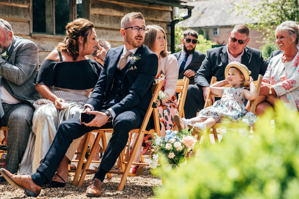 Guest makes a face at little girl during outdoor wedding ceremony at Ratsbury Barn.  Essex Documentary Wedding Photographer