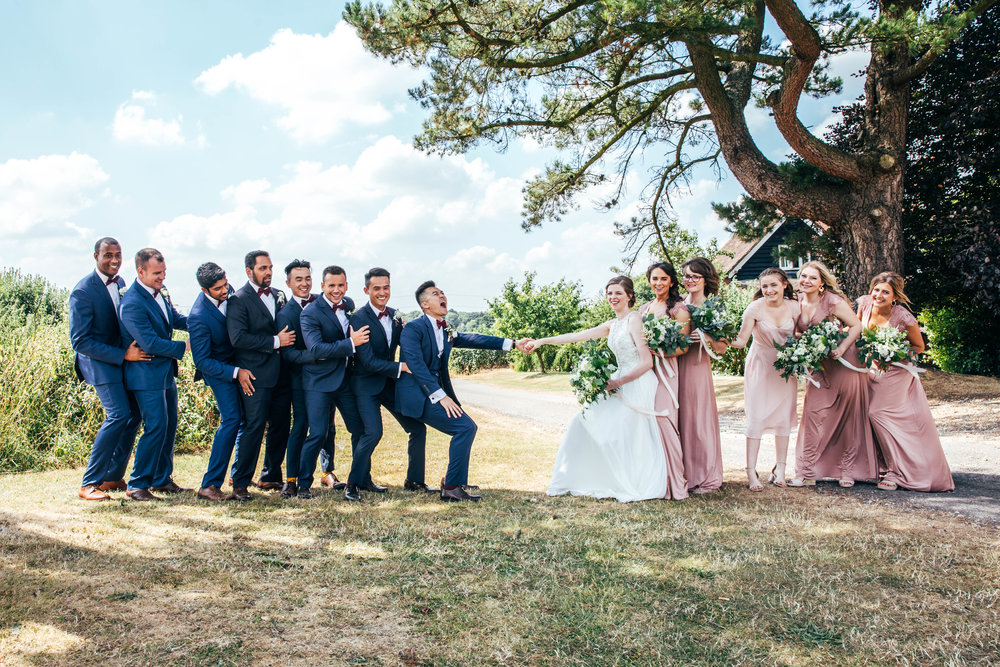 Bridesmaids and Groomsmen play tug of war at The Long Barn, Essex Documentary Wedding Photographer