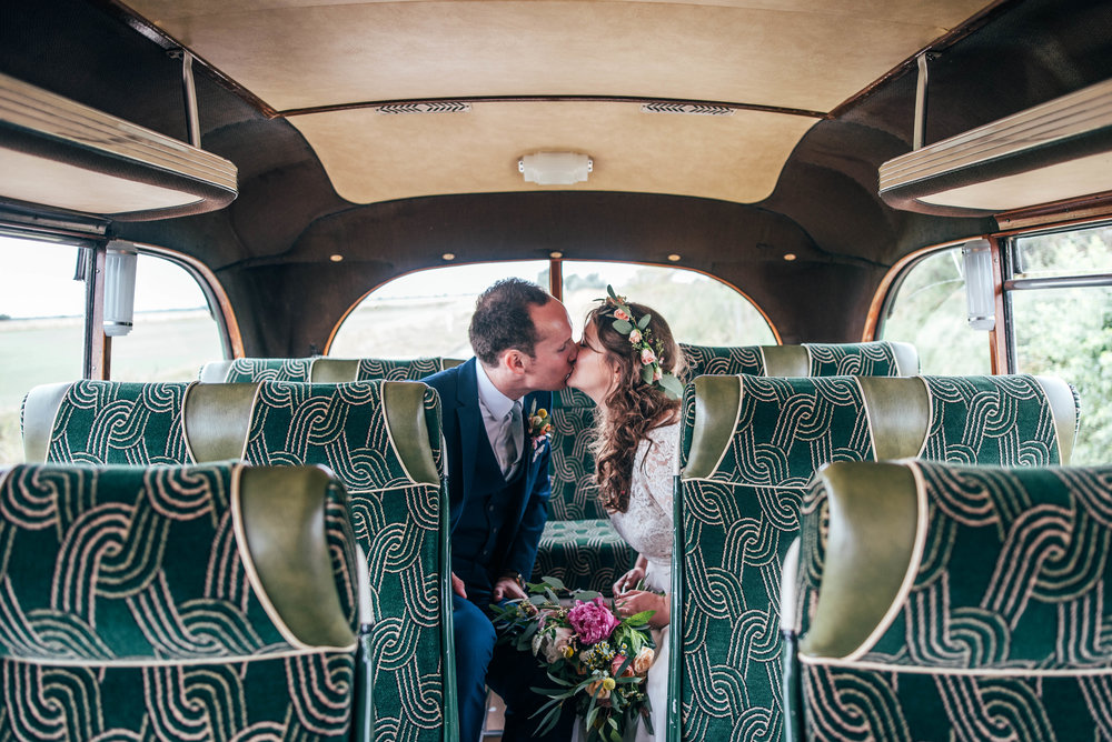 Bride and Groom kiss on back of vintage bus for boho wedding at Bedinghams Farm, Ely.  Essex Documentary Wedding Photographer