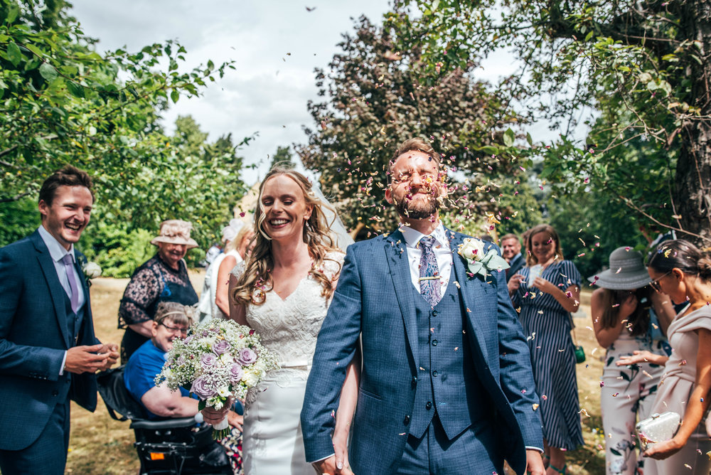 Groom gets confetti in the face for riverside wedding Essex Documentary Wedding Photographer