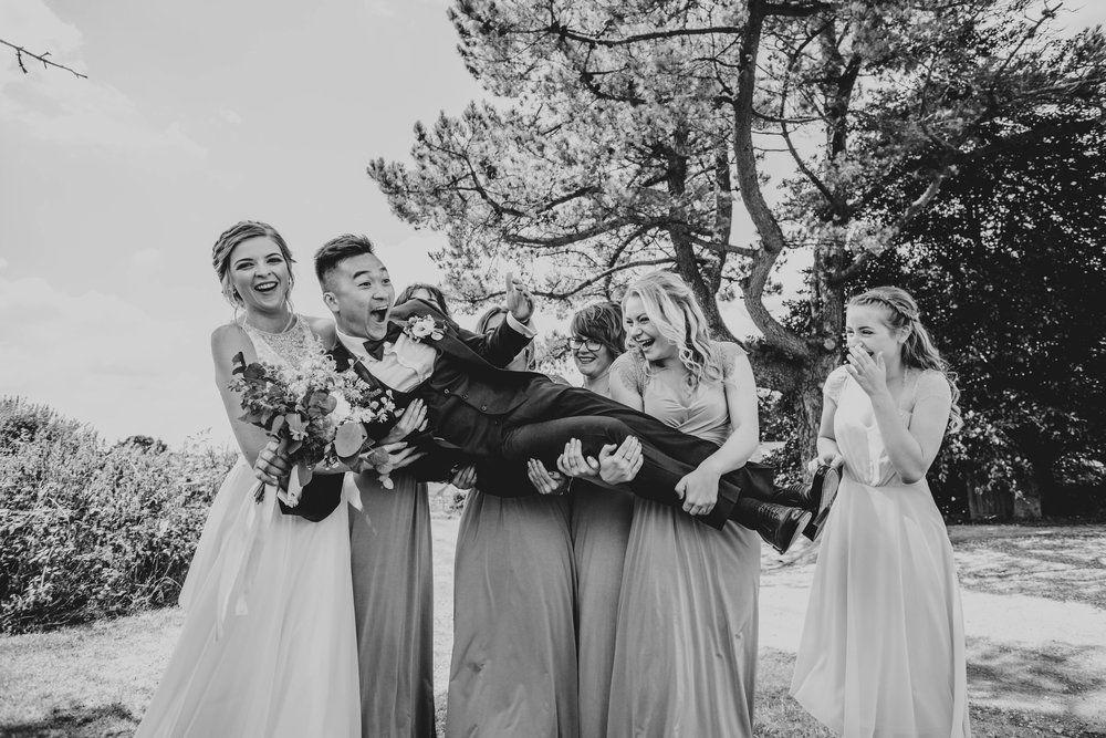 Laughing Bride and Bridesmaids lift up Groom at The Long Barn.  Essex Documentary Wedding Photography