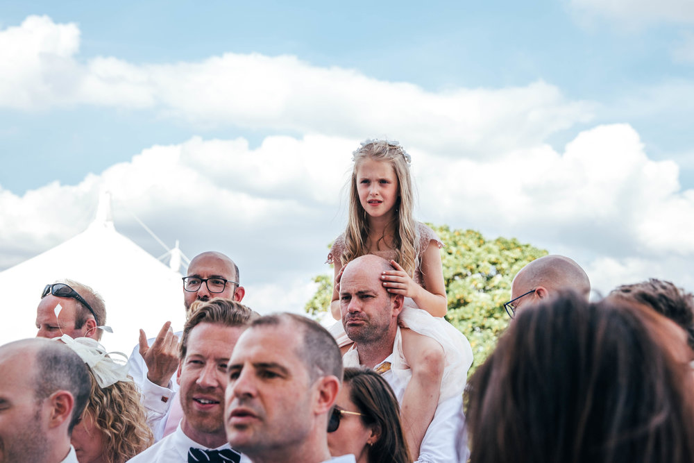 Little girl sits on Dads shoulders to watch England Quarter Final at DIY wedding.  Essex Documentary Wedding Photographer