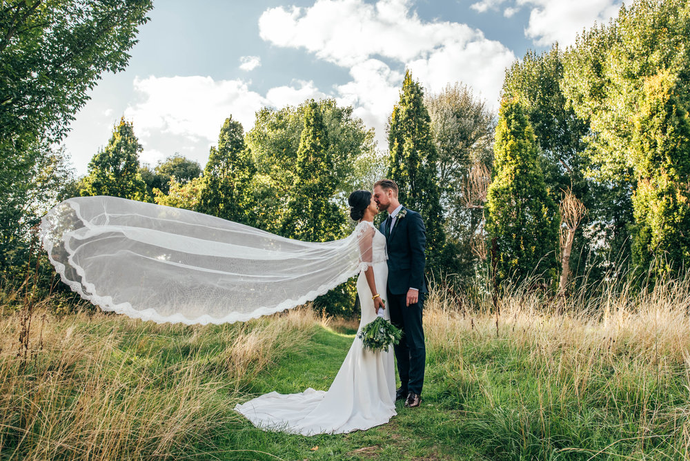 Bride with windswept veil kisses Groom at Mile End Ecology Pavilion.  Essex Documentary Wedding Photographer
