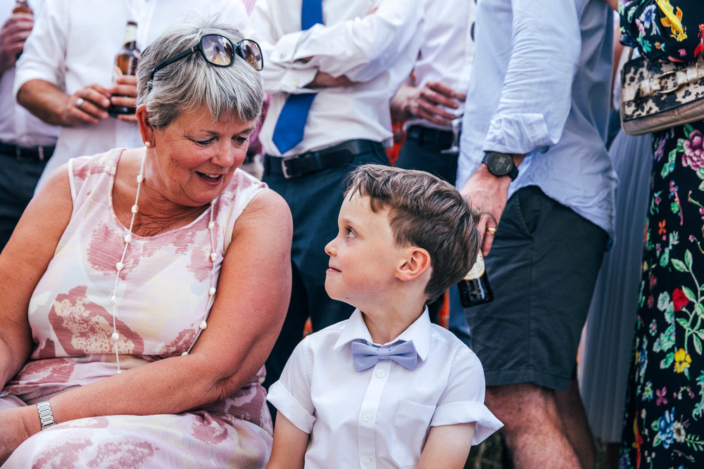 Little boy looks up at wedding guest outdoor DIY wedding Essex Documentary Wedding Photographer