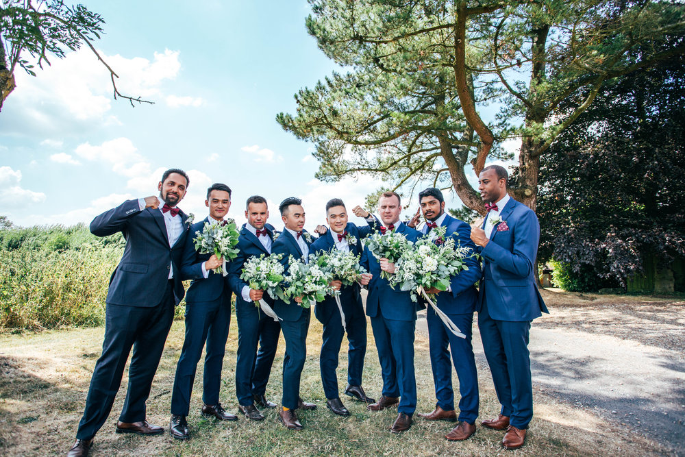 Groomsmen pose with bouquets at The Long Barn, Essex Documentary Wedding Photographer