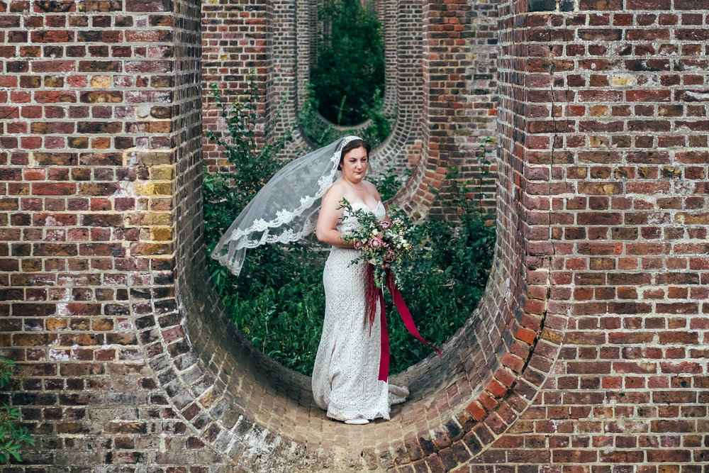 Bride in veil at Chappel Viaduct. East Anglian Railway Museum. Essex Documentary Wedding Photographer