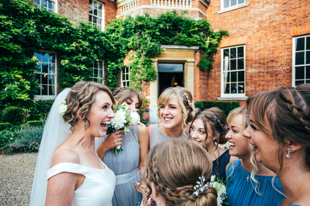 Beaming Bride is surrounded by Bridesmaids. Hedingham Castle.  Essex Documentary Wedding Photographer