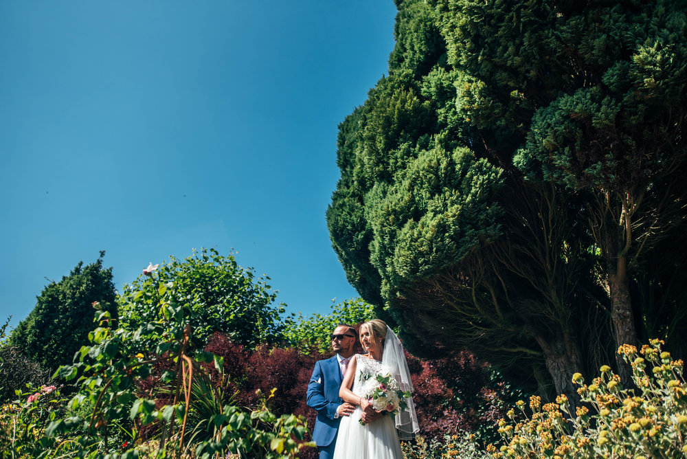 Bride and Groom under blue summer sky at Parklands Quendon Hall.  Essex Documentary Wedding Photographer