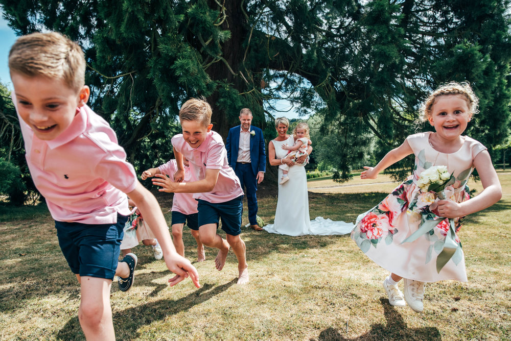 Bride and Groom laugh as their kids run towards camera at Ashdown Park Hotel.  Essex Documentary Wedding Photographer