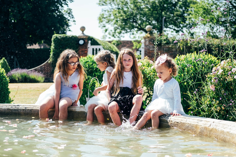 Little girls sit in Fountain for hot summer wedding at Quendon Hall.  Essex Documentary Wedding Photographer