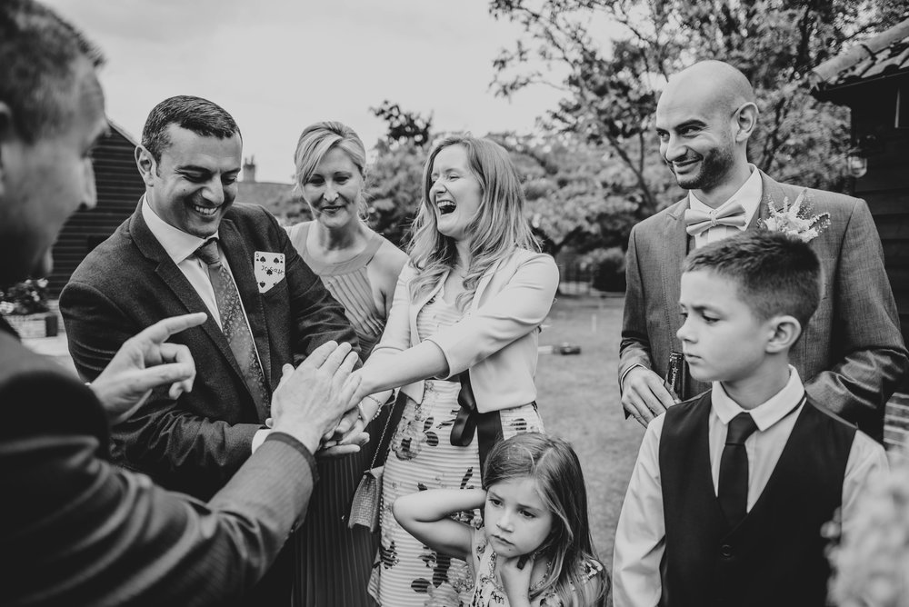 Laughing Wedding guests watch magic trick at Blake Hall, Ongar.  Essex documentary Wedding Photographer