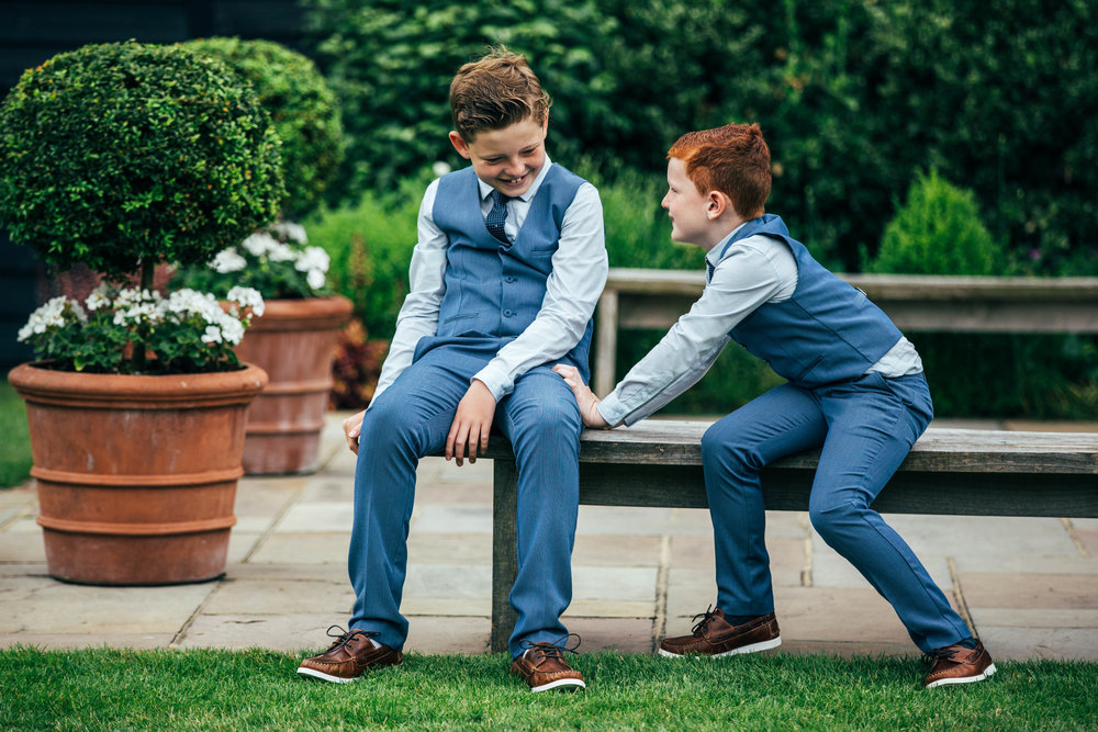Boy tries to push his brother off bench at Blake Hall, Ongar.  Essex Documentary Wedding Photographer