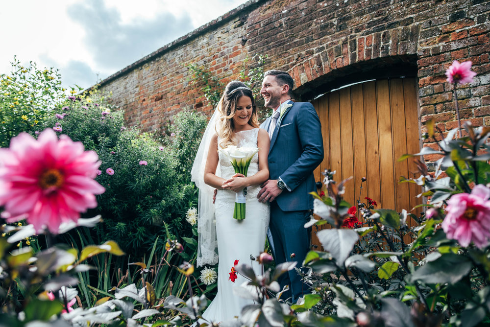 Laughing Bride and Groom in walled gardens at Blake Hall, Ongar.  Essex Documentary Wedding Photographer